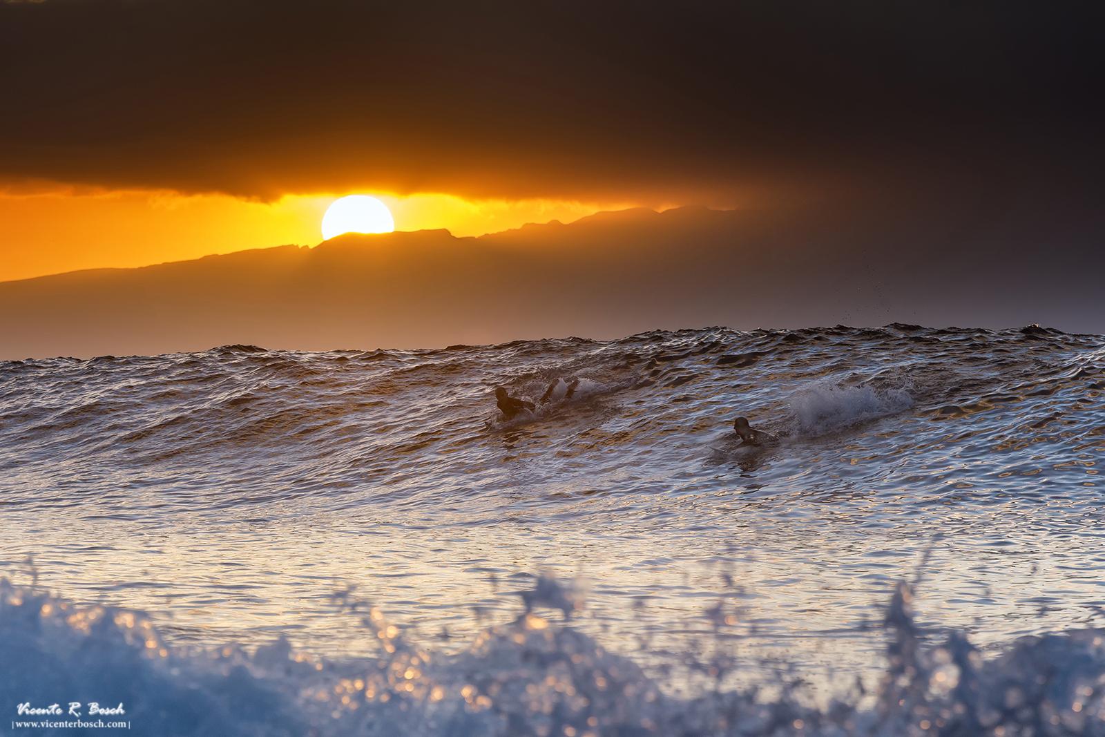 Surfers sobre la cresta de la ola al atardecer